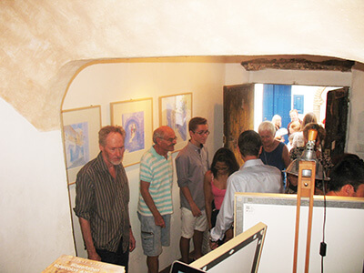 Photo of people visiting the art exhibition in Frigiliana of original watercolour paintings by Klaus Hinkel